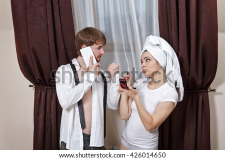 Morning couples. Husband and wife are going to work. Man talking on the phone and asks the girl to hurry. Girl doing make-up with a towel on her head. - stock photo