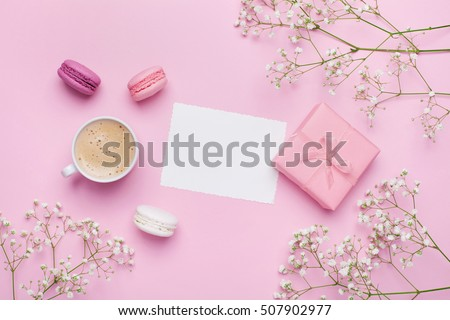 Morning cup of coffee, cake macaron, gift or present box and flower on pink table from above. Beautiful breakfast. Flat lay style.