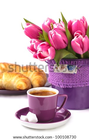 Morning cup of espresso with pink  tulips and croissants