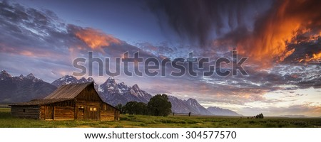 Morning drama in the skies above a Mormon Row barn in Wyoming's Grand Teton National Park. - stock photo