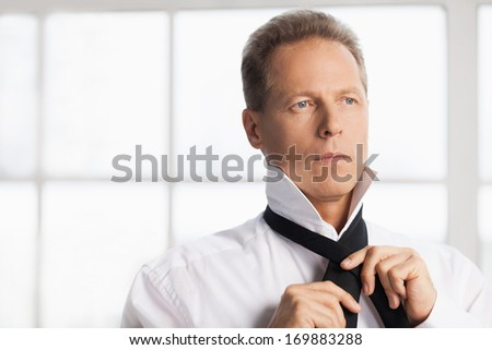 Morning dress up. Confident mature man in white shirt tying  his necktie and looking away