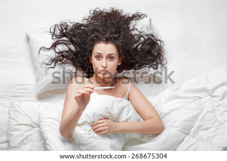 Morning fever. Upset young beautiful woman lying in he bed, holding thermometer. Top view. - stock photo