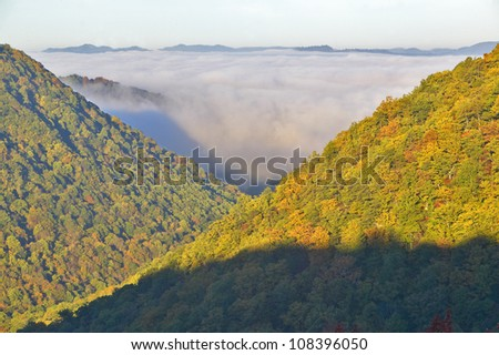 Morning fog at sunrise in autumn mountains of West Virginia in Babcock State Park - stock photo