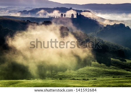 Morning fog in the valley between the hills - stock photo