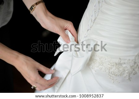 Morning gathering of the bride. Women's hands tie a bow from a ribbon on a wedding dress