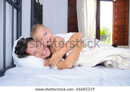 Morning. Happy mom and her little son playing in the bedroom