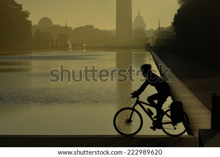 Morning haze and biker's silhouette in National Mall - Washington DC, United States of America - stock photo