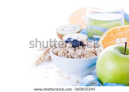 Morning healthy nutrition, diet frame with oatmeal porridge, fruits, mineral water and measuring tape. Perfect breakfast before workout - stock photo