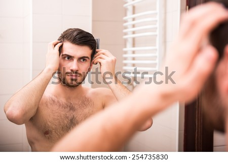 Morning hygiene. Handsome man is combing his hair, looking at the mirror. - stock photo
