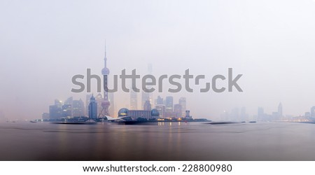 Morning in Lujiazui District, Shanghai. This morning suffered from low haze and pollution to give low visibility and poor air conditions. This panorama shows how the haze stifles the sunrise. - stock photo