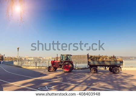 Morning in the city park. cleaning, pruning, tractor-trailer carrying wood. ecology concept - stock photo