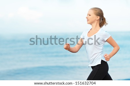 morning jog. young woman running on the beach on the coast of the Sea - stock photo