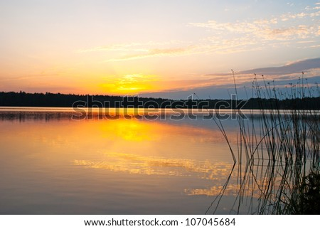 Morning lake landscape with sunrise over forest - stock photo