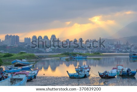 Morning landscape at dawn with sun beams shining through heavy clouds, stranded boats by riverside during a low tide & buildings in background ~ Beautiful sunrise scenery by Tamsui River Taipei Taiwan - stock photo