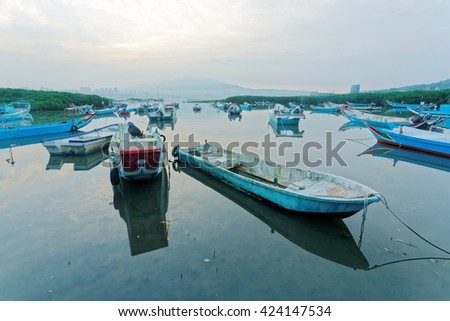 Morning landscape of stranded boats on Tamsui river during a low tide & foggy mountains in distant background under moody sky, Taipei Taiwan ~ Scenery of beautiful sunrise by Tamsui river Taiwan - stock photo