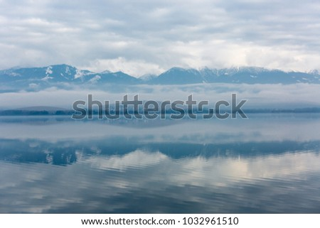 morning landscape with lake and fog in mountains