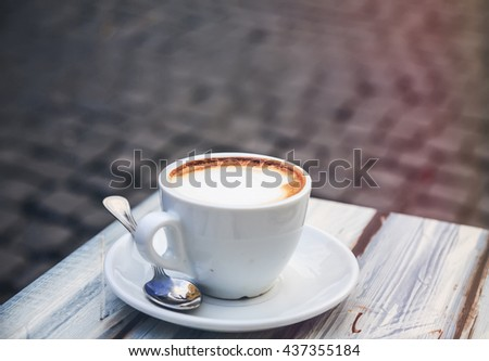 Morning light cup of cappuccino, cup of coffee, cup of coffee on brown wooden table  - stock photo