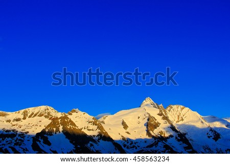 Morning light mountains with blue sky without clouds. Mountains in the Alps. Mountain scenery in winter. Grossglockner ountain in Hohe Tauern, Austria. Beautiful winter mountain landscape with snow - stock photo