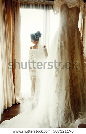 Morning light shines over pretty bride in long veil