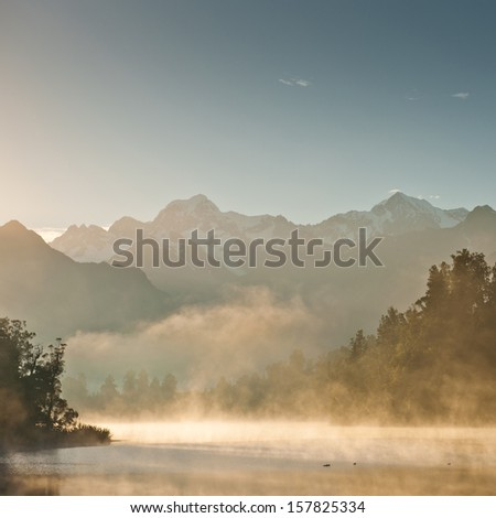 Morning mist by the lake - stock photo