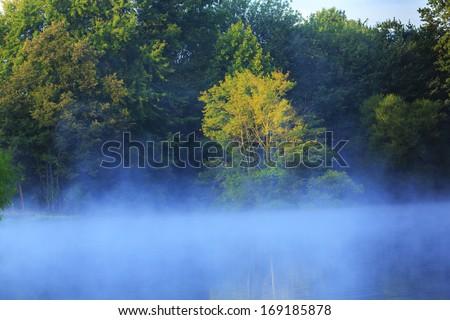 Morning mist raising on a lake - stock photo