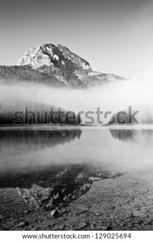 Morning mountain landscape with fog the lake black and white - stock photo