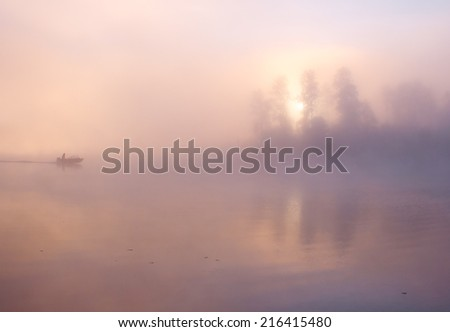 Morning nature misty scene: sky, water, trees, sun at sunrise visible through the fog  and lonely fishing boat with fisher reflected on the water surface (lake, river, pond). The Seliger lake (Russia) - stock photo
