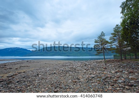 Morning norwegian landscape with mountains and mist over the lake - stock photo