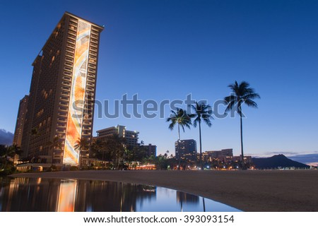 Morning on Waikiki Beach with palm trees and water reflecting the sky