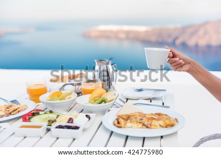 Morning person drinking coffee cup at breakfast table with mediterranean sea view. Woman eating at restaurant outside terrace patio on Santorini, Greece, Europe destination summer vacation. - stock photo