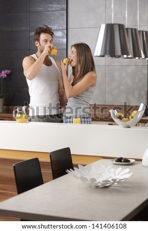 Morning picture of young couple in the kitchen with apple and orange juice. - stock photo