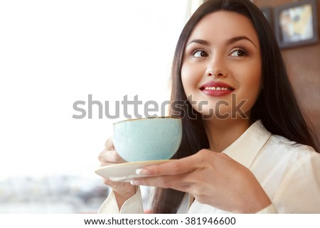 Morning pleasure. Closeup shot of a gorgeous happy woman having a cup of coffee smiling looking away