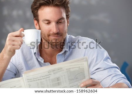 Morning portrait of handsome guy reading newspaper and holding coffee cup. - stock photo