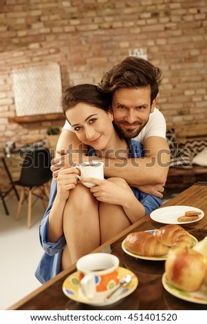 Morning portrait of happy loving couple embracing, having breakfast together at home. - stock photo