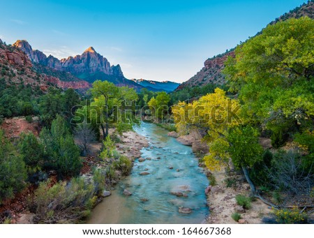Morning rays illuminate fall colors along the Virgin River and Watchman Peak, Zion National Park, Utah - stock photo