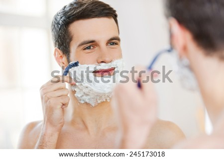 Morning routine. Handsome shirtless young man shaving his face and smiling while standing in front of the mirror - stock photo