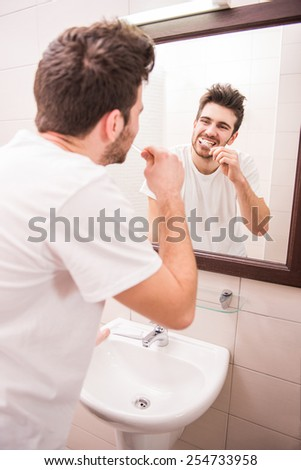 Morning routine of washing the teeth. Rear view of handsome young man is brushing teeth with toothbrush. - stock photo