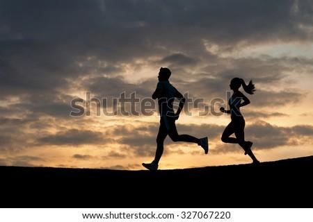 Morning running. Running athletes. Silhouette of runner on evening scamper. - stock photo