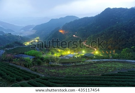 Morning scenery of tea gardens before daybreak in a deep blue mood with beautiful lights from the village in the valley and traffic trails on the highway by the mountainside in Ping-ling Taipei Taiwan - stock photo