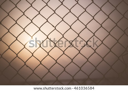 Morning sky at sunrise shining through a metal wire mesh fence.