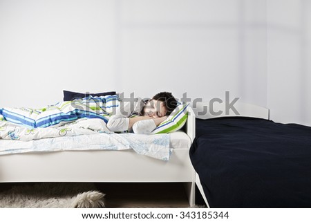 Morning sleep of caucasian boy laying down in bed at sunny room - stock photo