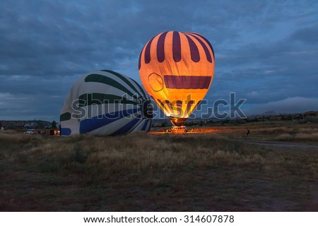 Morning start of a Hot air balloons (atmosphere ballons) flying over mountain landscape at Cappadocia, UNESCO World Heritage Site since 1985) - Turkey - stock photo