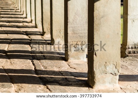 Morning sun illuminating massive stone pillars at Angkor Wat Temple. - stock photo