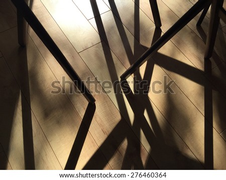 Morning sun shadows of a group of stacking trays with legs on the floor - stock photo