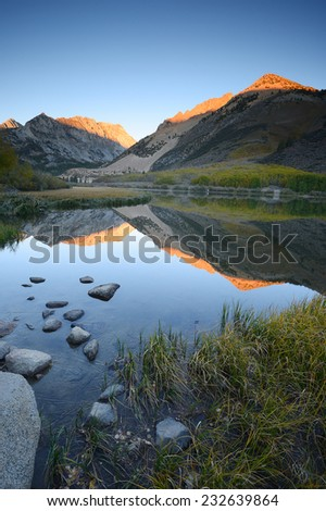 morning sunlight over mountain behind north lake at sierra nevada range - stock photo