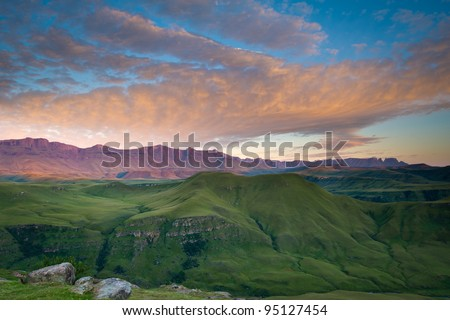 Morning sunlight reflects beautiful hues of orange on clouds above the famous Drakensberg Mountain range. - stock photo