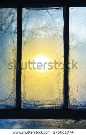 Morning sunlight shines through a frosted window. - stock photo