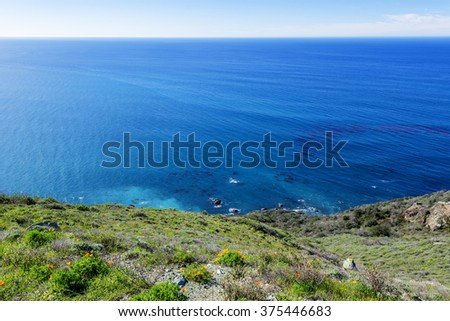 Morning sunrise, beautiful shimmering blue sea & sky, aquamarine waters, gentle surf, along steep sheer jagged cliffs, traveling the Big Sur Highway, on the California Central Coast, near Cambria CA.