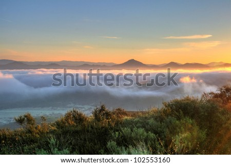 morning sunrise with mountain peaks rising over clouds in HDR in California - stock photo