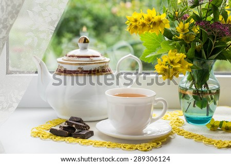 Morning tea near the window: a cup of tea, pieces of chocolate, kettle and a bouquet of flowers in a vase. Seen through the glass visible of green plants. Selective focus - stock photo